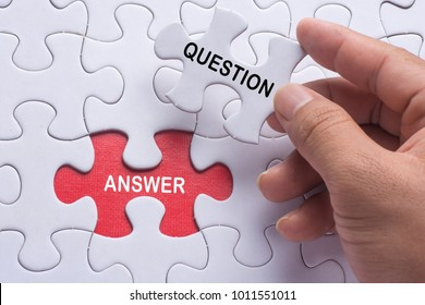 Hand holding piece of jigsaw puzzle with word question & answer