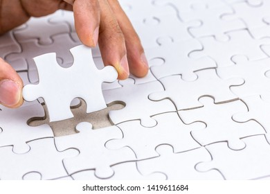 Hand holding piece of jigsaw puzzle and put to complete the missing part.Fulfill and  fix the problem of incomplete.Business solutions for success and strategy concept.