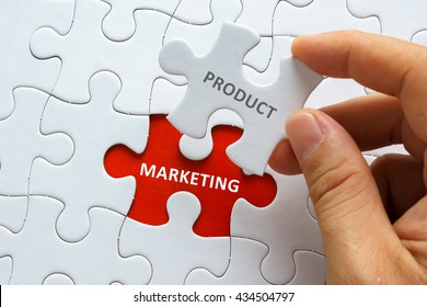 Hand holding piece of jigsaw puzzle with word PRODUCT MARKETING.