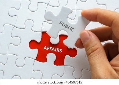 Hand holding piece of jigsaw puzzle with word PUBLIC AFFAIRS.