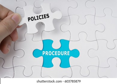 Hand holding piece of jigsaw puzzle with words Policies And Procedure.
