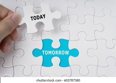 Hand holding piece of jigsaw puzzle with words Today and Tomorrow.