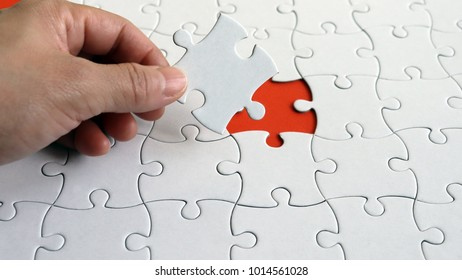 The hand holding a piece of the puzzle. A piece of a puzzle.