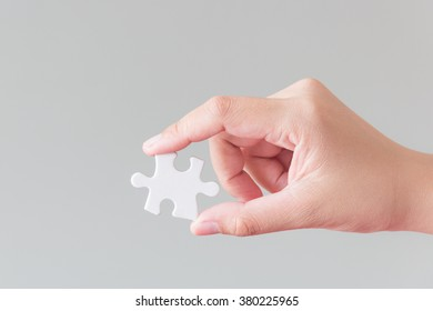 Hand holding a piece of puzzle jigsaw for metaphor like a key of business successful concept