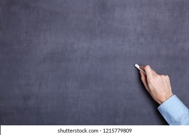 Hand holding a piece of white chalk and ready to start writing or drawing on a blackboard