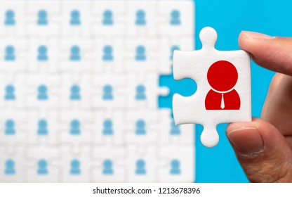 Hand holding piece of white jigsaw puzzle with icon. Human resource management and recruitment business concept