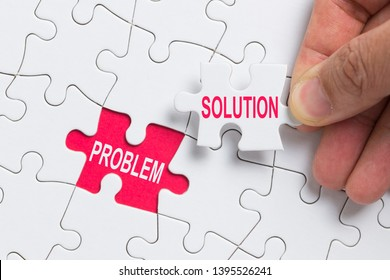 Hand holding piece of white jigsaw puzzle with word problem and solution.