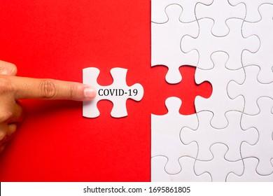 Hand, die ein Stück weißes Rätsel auf blauem Hintergrund mit dem Wort COVID-19 hält. Die Koronavirus-Pandemie verhindert soziale Distanz und Selbstisolierung.