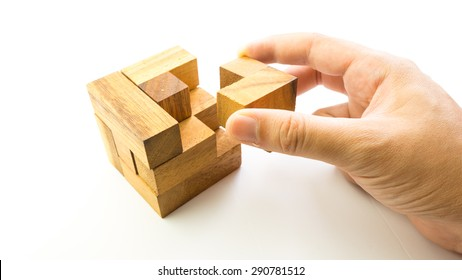 Hand holding piece of wooden block cube puzzle. Isolated on white background. Concept of complex and smart logical thinking. Slightly defocused and close up shot. Copy space.