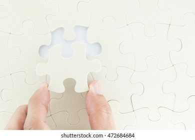 Hand holding piece of wooden jigsaw puzzle and fill in empty space , idea concept