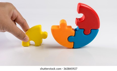 Hand holding pieces of puzzle to complete a pie chart. Concept of key to success. Slightly de-focused and close-up shot. Copy space.