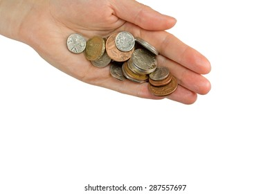 Hand is holding a pile of  British coins. All is isolated on the white background.