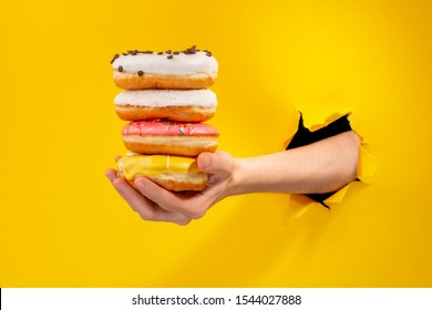 Hand holding a pile of different doughnuts, giving them through a torn hole in yellow paper background. Fresh bakery and discount concept.