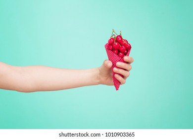 Hand holding pink cone with cherries