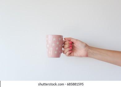 Hand holding pink mug