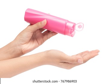 hand holding Pink Plastic bottle of shampoo isolated on white background