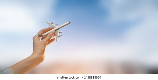 Hand holding a plane over blurred city background with sky.Tourism or travel concept