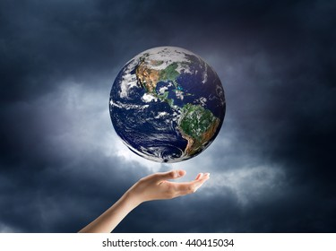 hand holding a planet in space. Elements of this image are furnished by NASA