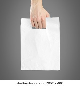 Hand holding plastic bag. Close up. Isolated on grey background.