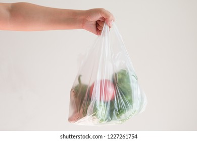 Hand holding a plastic bag of vegetables