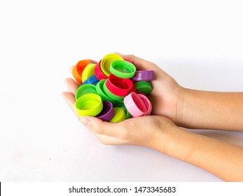 hand holding plastic bottles caps for recycling to conserve the environment, on white background