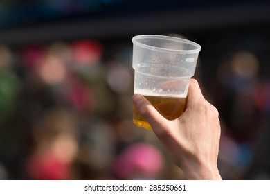 hand holding up plastic glass of beer during outdoor event