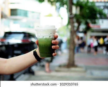 Hand holding plastic glass of iced matcha green tea latte with layer of cream cheese foam on blurred background, Summer refreshment drinks.