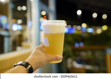 Hand holding a plastic glass of iced oolong tea (also called wulong or wu long) with layer of cream cheese foam on blurred background, Traditional Chinese and Taiwanese Beverage.