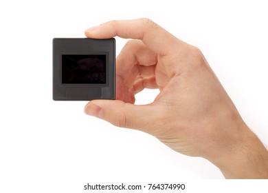 Hand holding plastic mounted slide on white background