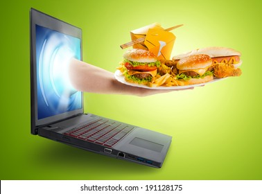 Hand holding a plate with food coming out of a laptop screen - Internet shopping concept.