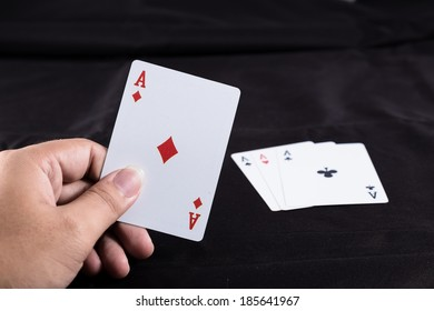 hand holding playing cards on black background