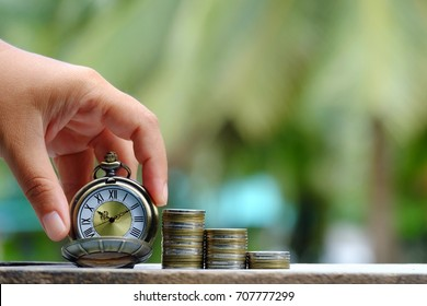 hand holding pocket watch and stack of coins on old wood table with nature copy space background, saving money and business concept