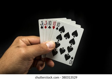 Hand holding poker cards to form a full on black background