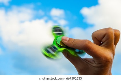 Hand holding popular green fidget spinner toy on sky background with copy space.