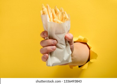 Hand holding a portion of French fries through torn yellow paper background. Yummy snack for lanch, fast food industry.