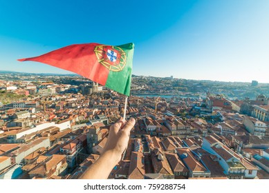 hand holding portuguese flag on aerial view of historic center of Porto in Portugal from Clerigos Tower, one of the landmarks and icon of Oporto. Urban cityscape with blue sky