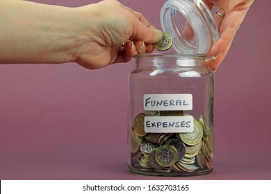 A Hand Holding A Pound Coin And Putting It In To A Glass Jar. Saving Money To Pay Funeral Expenses Concept.