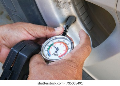 Hand holding pressure gauge for car tire pressure measurement. Vehicle safe concept.