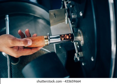 hand holding a probe of fresh roasted coffee beans in vintage color tone