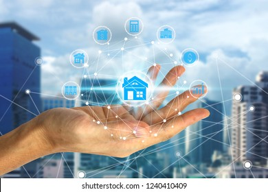 Hand holding with property investment icons over the Network connection on property background, Property investment concept.