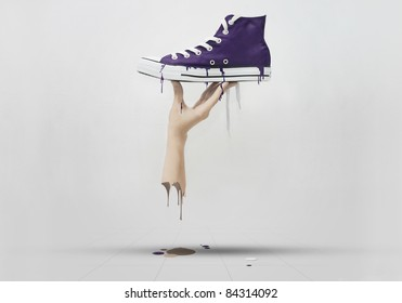 A hand holding a purple sneaker, melted all over the floor.
