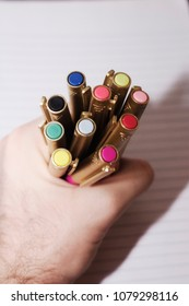 A hand holding a rainbow of colored pens on lined paper.
