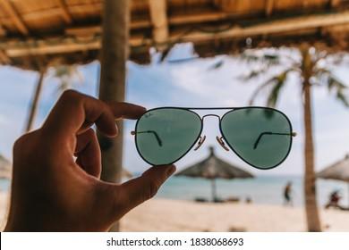 Hand holding Ray-Ban Aviator sunglasses on Ky Co beach. KY CO, QUY NHON, BINH DINH, VIETNAM - AUGUST 21, 2019.