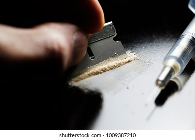 Hand Holding a Razor blade and Needle isolated on a black background. Drug Addiction Overdose on pills.