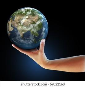 Hand holding realistic small globe symbolizing environmental care, facing Asia