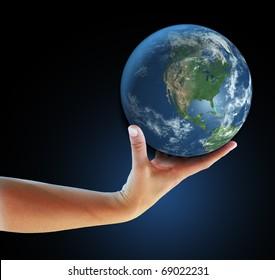 Hand holding realistic small globe symbolizing environmental care, facing North America