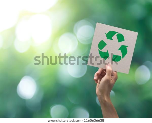 Main tenant un symbole de recyclage sur fond vert flou. éco et sauvez le concept de la terre.