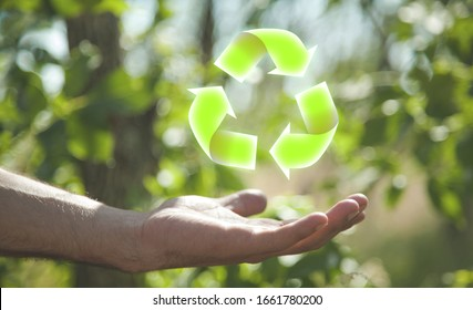 Hand holding Recycling symbol in nature.