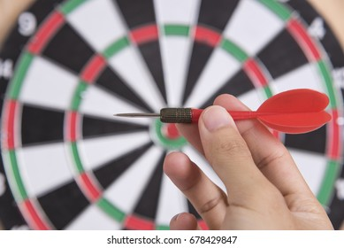 hand holding red arrow target center of dartboard. concept business goal to marketing success.