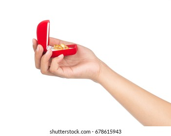 hand holding a red box with a gold ring isolated on a white background.
